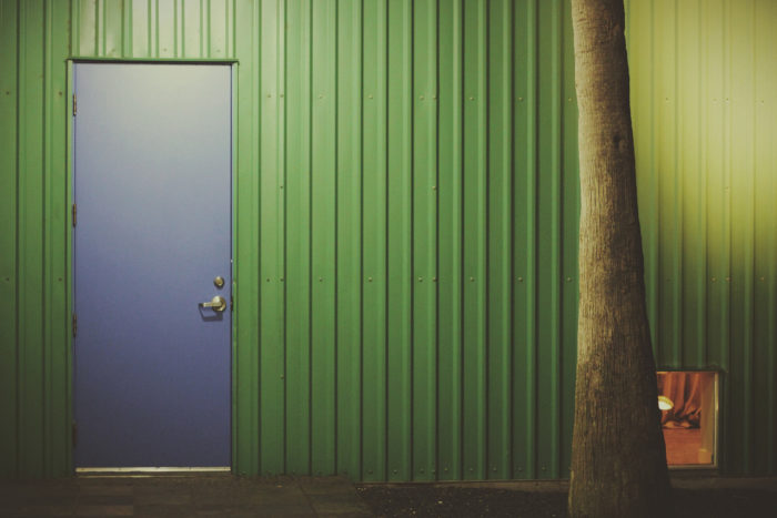 Closed blue door, in a green metal wall